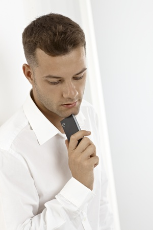 Young daydreaming man holding mobile in hand, waiting for phone call. Stock Photo - 15965778