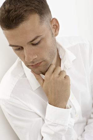 Portrait of young man, looking down thinking, daydreaming. Stock Photo - 15965781