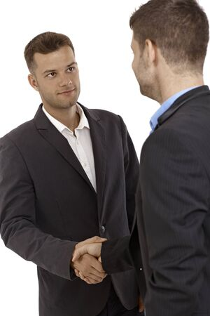 bristly: Young businessmen shaking hands, introducing themselves.