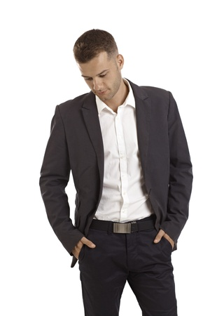 Young businessman thinking, standing with hands in pockets. photo
