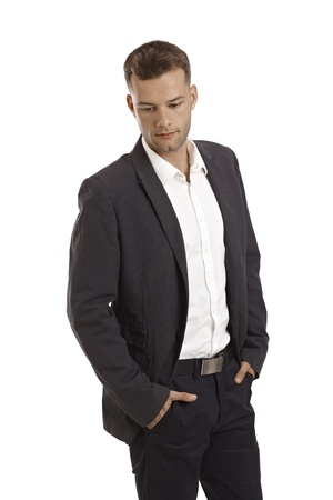 man looking down: Young businessman standing with hands in pockets, looking down. Stock Photo