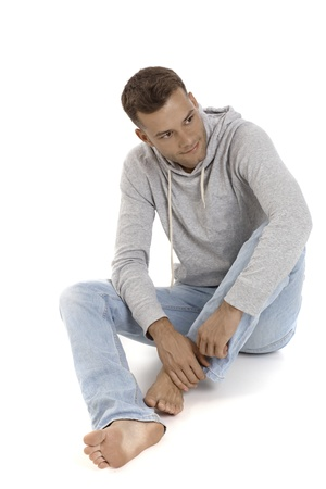 barefoot man: Casual young man in jeans and hoody sitting on floor, looking away.