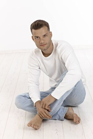 bristly: Casual young man sitting on floor in jeans. Stock Photo