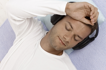 Young man lying on floor listening to music through headphones, eyes closed. photo