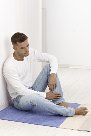 stubbly: Young man sitting on floor at home, looking sad.