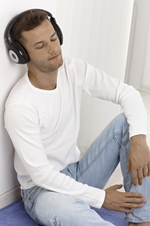 Young man listening to music through headphones, sitting on floor eyes closed. photo