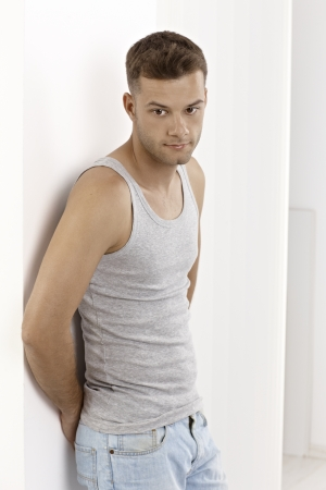 Casual young man standing by wall in undershirt. photo