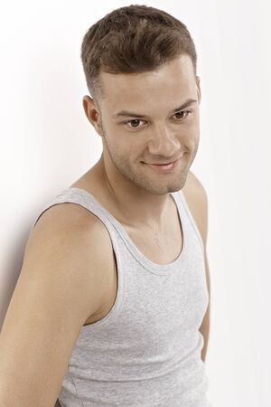 Portrait of young man wearing undershirt, smiling. Stock Photo - 15965792