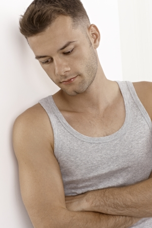 Portrait of daydreaming young man in undershirt, looking down. Stock Photo - 15965751