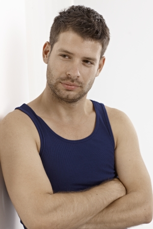white singlet: Young man standing arms crossed in dark blue vest, looking away, daydreaming.
