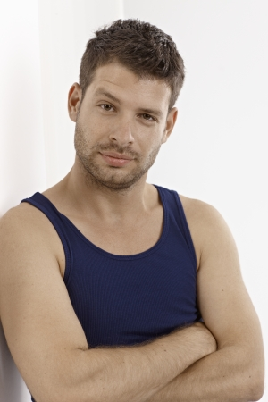 Portrait of young man in dark blue vest, standing arms crossed. Stock Photo - 15965749