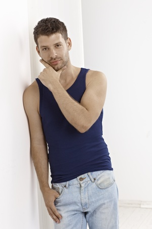 Casual young man leaning against wall, wearing undershirt and jeans. photo