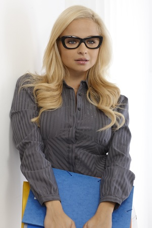Pretty blonde secretary holding files wearing black framed glasses. photo