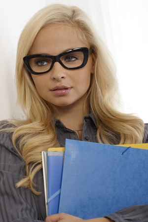 Pretty young blonde secretary holding folders, wearing glasses. photo