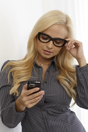 Blonde young woman using mobilephone, wearing glasses. photo