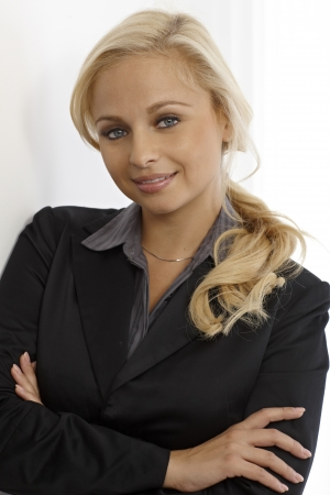 indoor photo: Portrait of happy smiling blonde businesswoman standing arms crossed.