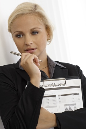 Young attractive blonde businesswoman thinking. photo