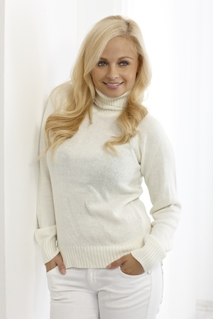 turtleneck: Confident young woman in white outfit leaning against wall, smiling with hands in pockets. Stock Photo