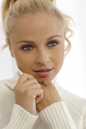 Closeup portrait of beautiful young blonde woman in white pullover.