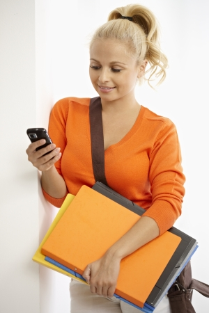 Pretty blonde student holding folders, using mobile phone. photo