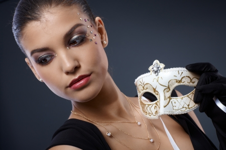 woman looking down: Masquerade elegance of attractive woman wearing glamorous makeup with strasses, holding fancy carnival mask. Stock Photo