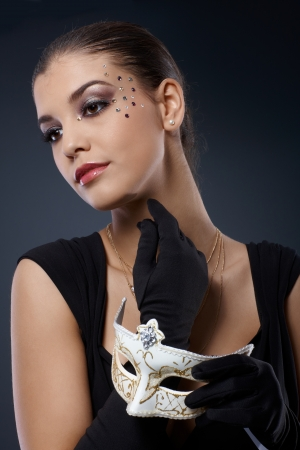 fantasize: Beauty in sparkly luxury makeup and gloves posing with carnival mask handheld.