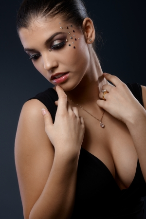 Sexy portrait of woman posing in seductive black dress with cleavage in fancy makeup with straplesses    photo