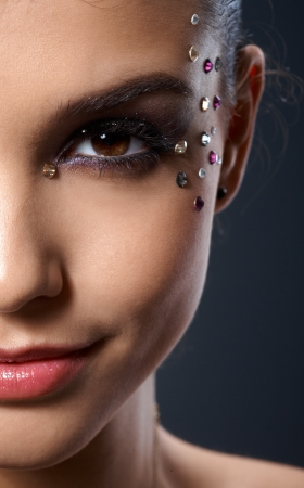 rhinestones: Makeup with rhinestones, closeup portrait of part face of smiling beauty
