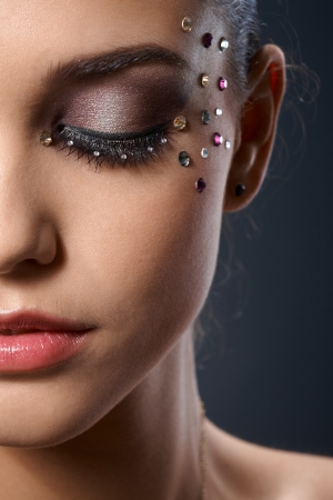 glitter makeup: Partial facial portrait of beautiful woman wearing luxury makeup with straplesses, closed eyes
