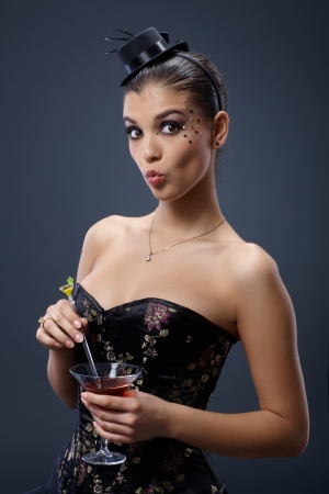 Woman with round lips looking surprised, in fancy dress, stirring cocktail glass   65533; photo