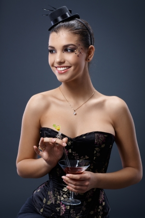 Smiling woman posing in fancy dress and little hat, stirring cocktail glass handheld     photo