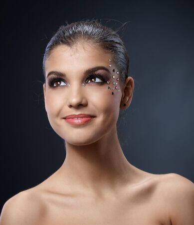 glitter makeup: Closeup portrait of happy smiling beautiful woman with fancy makeup with colorful rhinestones.