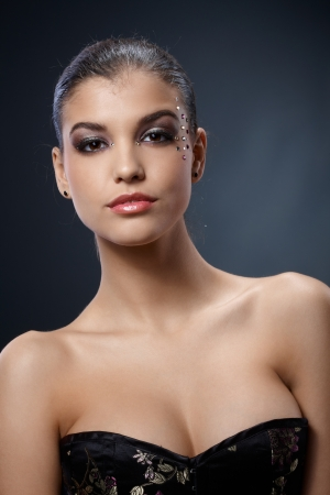 Sexy elegant beauty with nice cleavage and luxury makeup with strasses, seductive smile. photo