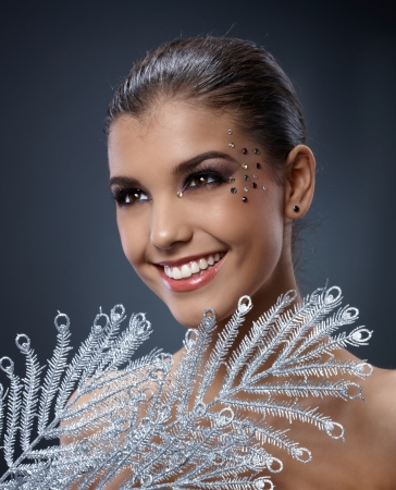 rhinestones: Happy woman with fancy sparkly makeup and silver branch fan, smiling. Stock Photo