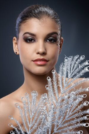 Portrait of smart beauty in sparkly makeup smiling with silver fan. Stock Photo - 16117564