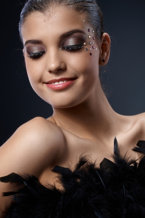 black boa: Happy woman with glittering extravagant makeup posing with black boa, smiling.
