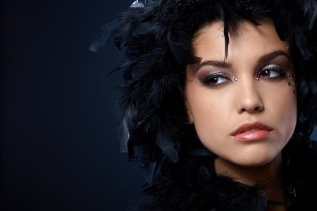 black boa: Mystical look of beauty covered in black feather boa, wearing makeup with strasses.