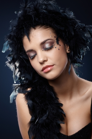 black boa: Elegant and beautiful girl with sparkly makeup and black boa posing with eyes closed. Stock Photo