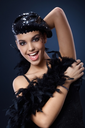 black boa: Attractive woman enjoying posing and smiling in extravagant party outfit, fancy makeup, black sequin hat and feather boa.