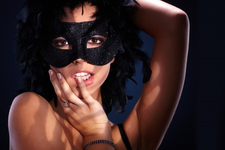 Seductive portrait of attractive woman in posing in black boa and sparkly masquerade. photo