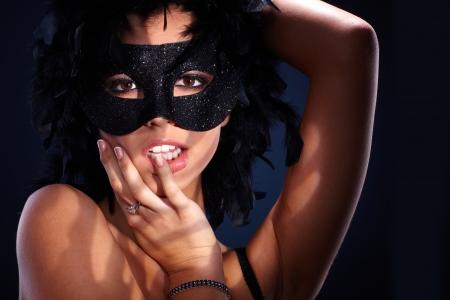 feather boa: Seductive portrait of attractive woman in posing in black boa and sparkly masquerade.