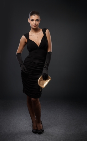 Beauty ready for elegant party in fancy black cocktail dress, gloves, high heels and golden handbag. Stock Photo - 16117530