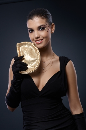 Happy sexy woman smiling, posing with golden handbag in fancy black evening dress. photo