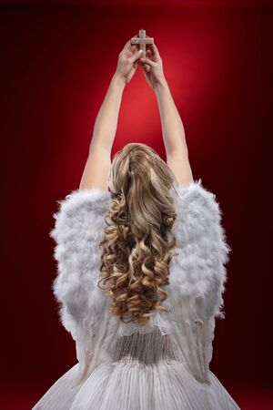 Back view of praying angel holding crucifix over red background.