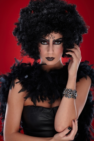 Devil woman with black wig and boa and red horns. photo