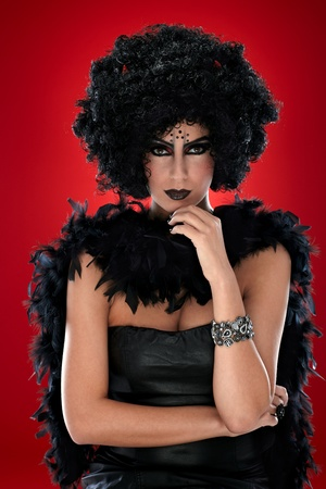 Young woman dressed like a black bogy with black makeup. photo