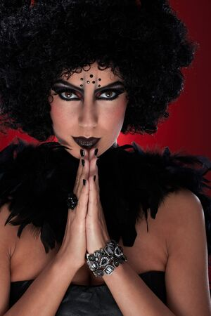 Evil woman in black wig and boa praying. photo