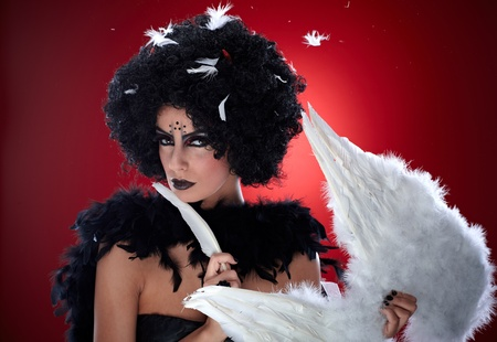 Evil woman holding angel wings, pulling out feathers. photo