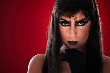 rhinestones: Young woman with professional black makeup and evil eyes. Stock Photo