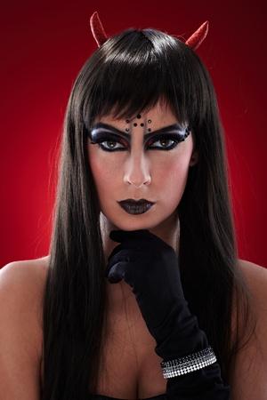 satanas: Retrato de mujer espantajo negro con cuernos y pelo largo, mirada malvada.